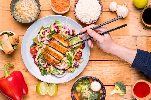 Close-up, de, um, pessoa, mão, buscar, a, filetes, com, chopsticks, ligado, tabela