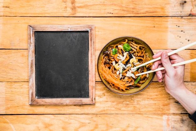 Close-up, de, um, pessoa, mão, colheita, a, noodles, com, chopsticks, perto, a, em branco, ardósia, ligado, tabela