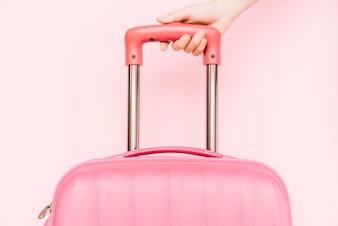 Close-up, de, um, pessoa, mão segura punho, de, viagem, bagagem, contra, fundo cor-de-rosa