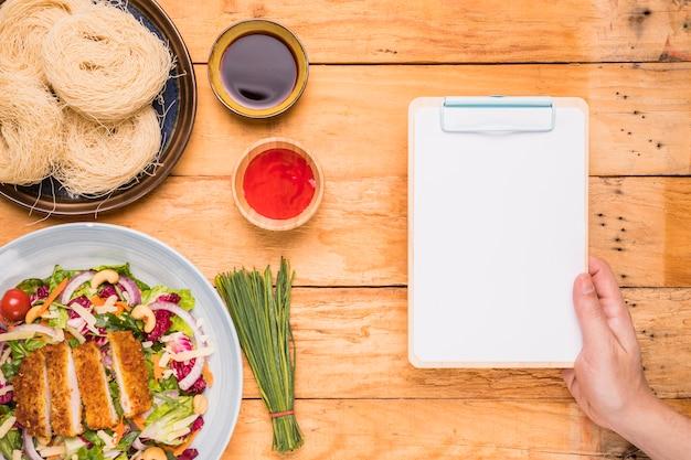 Close-up, de, um, pessoa, mão, segurando clipboard, perto, a, tradicional, comida tailandesa, ligado, tabela madeira