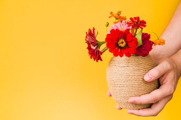 Close-up, de, um, pessoa, mão, segurando, vaso flor, contra, fundo amarelo