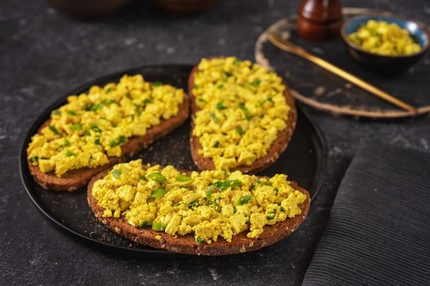 Close-up de um prato com sanduíches de salada de ovo vegan amarelo brilhante