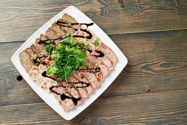 Close-up de um prato quadrado cheio de uma carne recheada, decorado com folhas verdes e molho de soja na mesa de madeira.