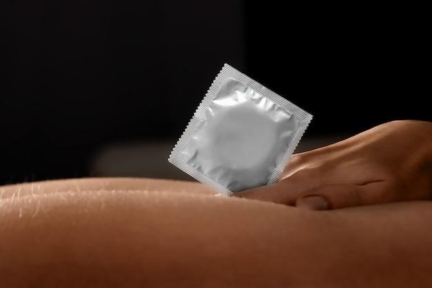 Close-up de um preservativo em uma mão feminina. preliminares sexuais, contracepção, conceito de sexo seguro, proteção contra doenças venéreas.