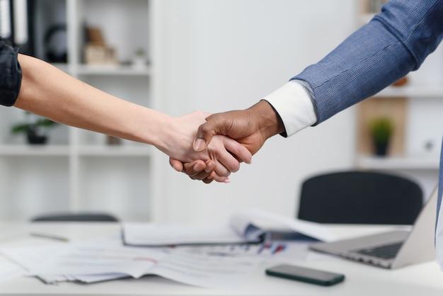 Close-up de um preto e branco mãos tremendo sobre um acordo de bons negócios.