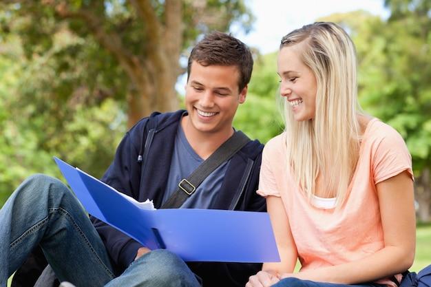 Close up de um professor sorridente ajudando um adolescente a rever