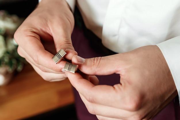 Close-up de um quadro cortado da mão de um homem em um terno de negócio, camisa branca.