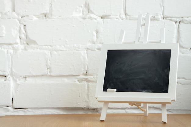 Close-up de um quadro de giz miniatura com manchas de giz e giz em uma parede de tijolos brancos