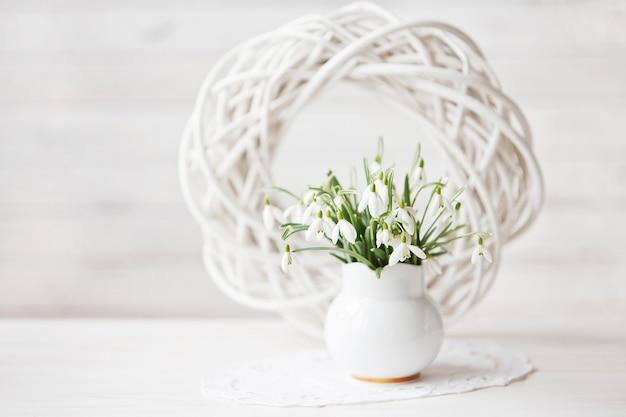 Close-up de um ramalhete de flores da mola dos snowdrops em um fundo de madeira branco.
