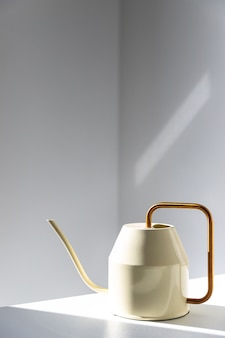 Close up de um regador metálico branco elegante com bico longo e fino e cabo circular fino amarelo na mesa, parede na superfície, dentro de casa. luz solar.