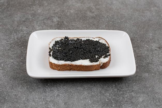 Close-up de um sanduíche de caviar preto em uma placa branca na superfície cinza