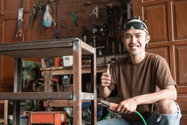Close-up de um soldador masculino sorrindo com um polegar para cima, enquanto segura um soldador elétrico em uma oficina de soldagem