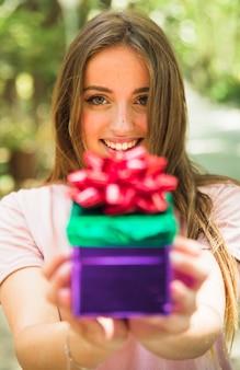 Close-up, de, um, sorrindo, mão mulher, segurando, valentine, presente