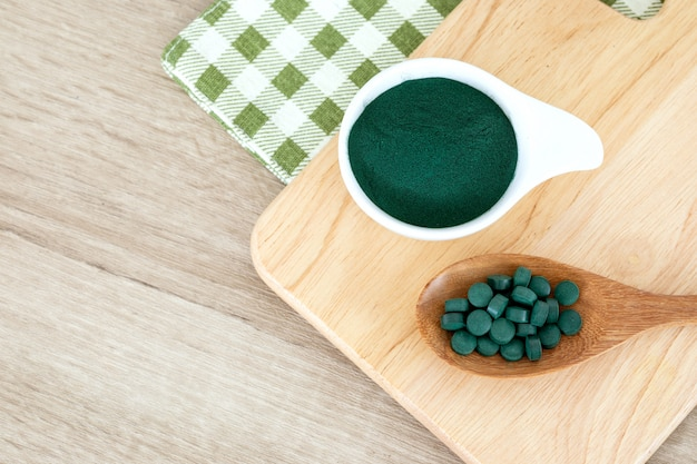 Close up de um spirulina em pó e spirulina comprimidos em colher, dieta saudável superalimento e uma nutrição de desintoxicação