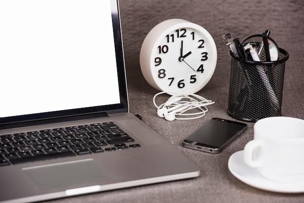 Close-up de um tablet digital aberto com despertador; telefone celular e material de escritório na mesa