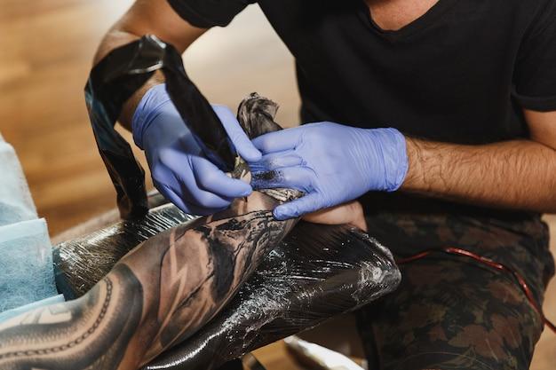 Close-up de um tatuador profissional fazendo uma tatuagem no braço de um jovem por uma máquina com tinta preta