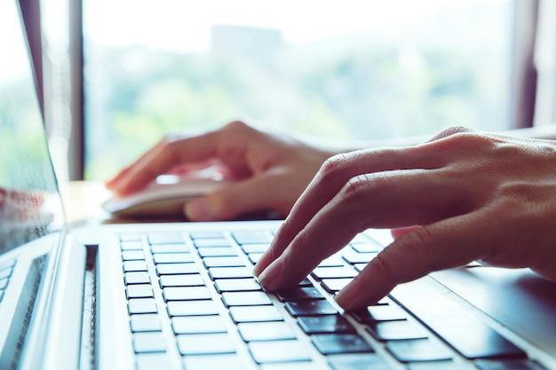 Close-up de um trabalhador usando um computador portátil. pressionando botões, digitando