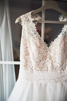 Close-up de um vestido de noiva de renda pendurado na janela