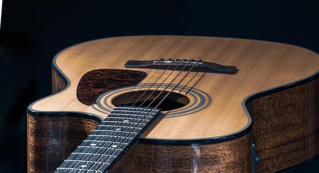 Close-up de um violão clássico em um fundo preto.