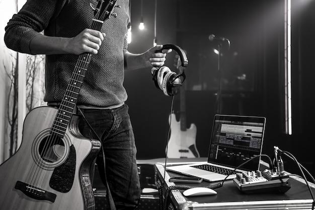 Close-up de um violão e fones de ouvido profissionais nas mãos de um homem em um estúdio de gravação.