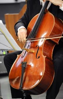 Close-up de um violoncelista tocando violoncelo