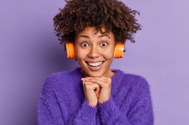Close-up de uma adolescente de cabelos cacheados olhando alegremente para a câmera mantendo as mãos sob o queixo sorrindo ouvindo música favorita usando um macacão quente