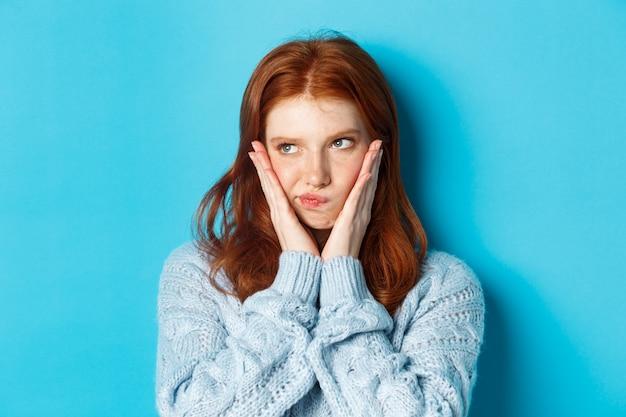 Close-up de uma adolescente problemática com cabelo vermelho, olhando para a esquerda, fazendo beicinho e parecendo mal-humorada na promoção, em pé sobre um fundo azul.