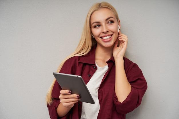 Close-up de uma adorável loira de cabelos compridos feliz em roupas casuais, mantendo a mão em seu pescoço e usando fones de ouvido, sorrindo alegremente em pé sobre um fundo cinza claro