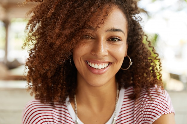 Close up de uma adorável mulher afro-americana com um sorriso largo, vestindo uma camiseta listrada, estando de bom humor, descansando no refeitório com os melhores amigos. mulher jovem sorridente de pele escura em poses internas
