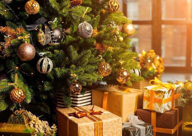 Close-up de uma árvore de natal decorada com bolas de ouro. debaixo da árvore de natal, um grande número de presentes de natal. conceito de férias de natal