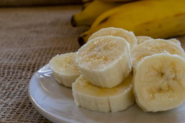 Close up de uma banana fatiada no prato e um cacho de bananas no fundo. foco seletivo