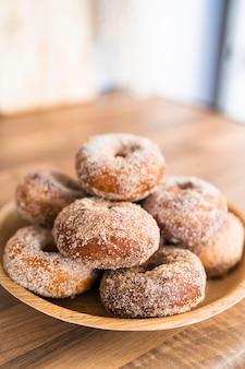 Close-up de uma bandeja de donuts de açúcar caseiro recém-assados em uma mesa de madeira em uma cozinha