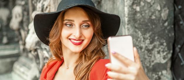 Close-up de uma bela jovem caucasiana tirando uma selfie no smartphone em pé e sorrindo contra um prédio antigo ao ar livre