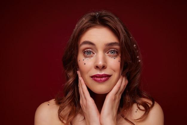 Close-up de uma bela jovem com cabelo castanho ondulado, usando maquiagem de noite enquanto posava, olhando com calma e tocando suavemente seu rosto