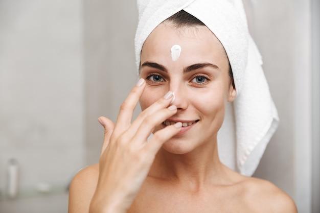 Close-up de uma bela jovem com uma toalha na cabeça, em pé no banheiro, aplicando creme facial