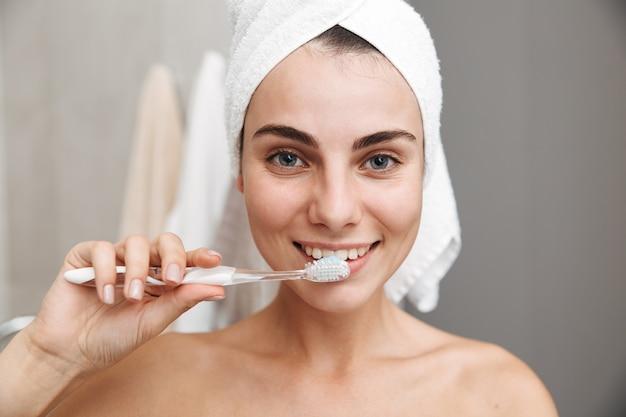 Close-up de uma bela jovem com uma toalha na cabeça, em pé no banheiro, escovando os dentes