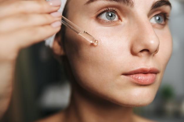 Close-up de uma bela jovem enrolada em uma toalha, aplicando óleo cosmético no rosto