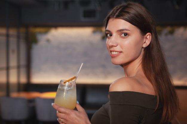 Close-up de uma bela jovem sorrindo por cima do ombro para a câmera, desfrutando de uma bebida no bar