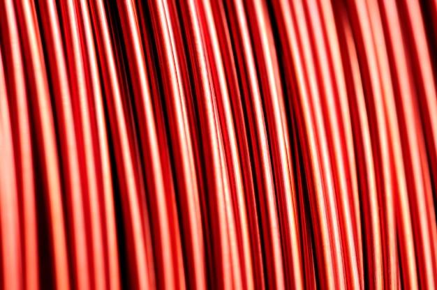 Close-up de uma bobina de fio de cobre vermelho na fabricação de peças elétricas