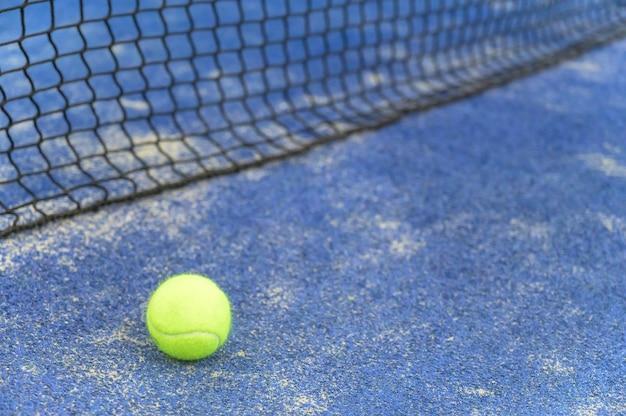 Close up de uma bola de tênis perto da rede