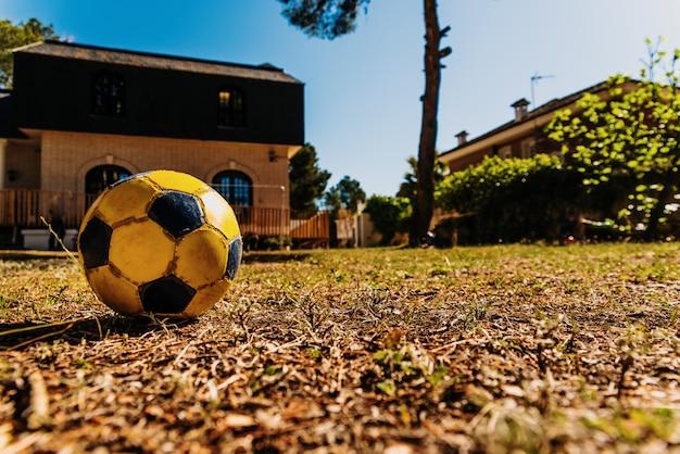 Close-up de uma bola desgastada velha do futebol na jarda de uma casa.
