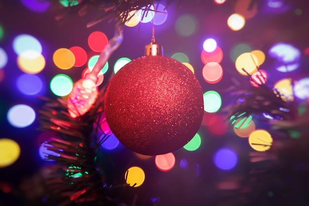 Close-up de uma bola vermelha brilhante de natal pendurado em uma árvore de natal no fundo muitas guirlandas brilhando em cores diferentes.