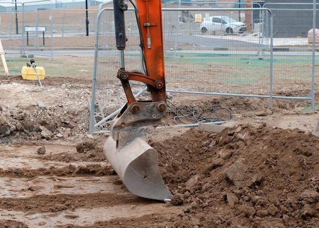 Close up de uma caçamba da escavadeira colocada no solo em posição segura