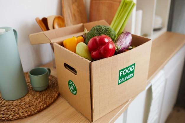 Close-up de uma caixa de papelão com legumes frescos na mesa para entrega de comida