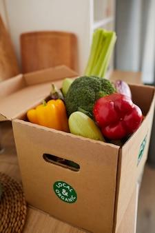 Close-up de uma caixa de papelão com legumes frescos sobre a mesa sendo entregue em casa