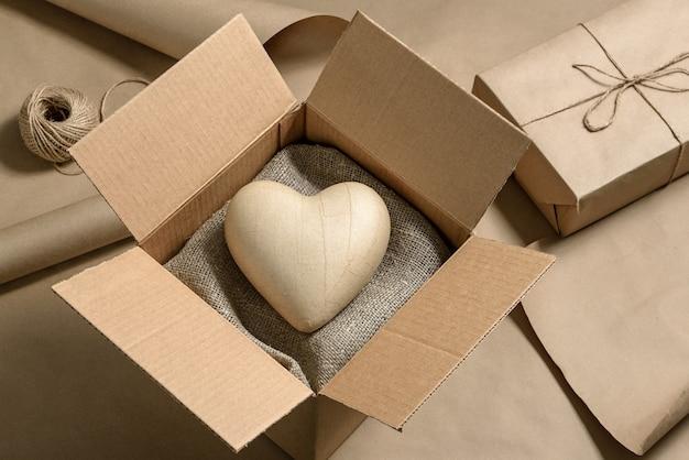 Close-up de uma caixa de papelão com um coração de papel dentro. conceito de presente do dia dos namorados.