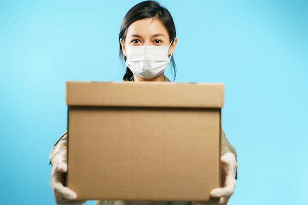 Close-up de uma caixa de papelão nas mãos de uma jovem mulher em uma máscara protetora médica e luvas em um fundo azul. entrega segura