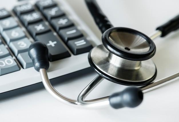 Close up de uma calculadora e um conceito de cuidados de saúde e despesas de estetoscópio