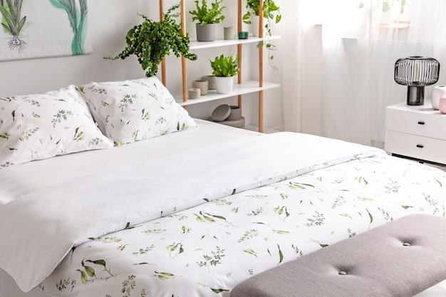 Close up de uma cama vestida com plantas verdes de algodão orgânico padrão de linho branco em uma foto real ensolarada