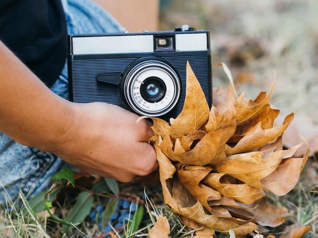 Close-up de uma câmera fotográfica realizada por uma mulher